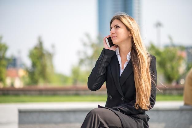 街の通りに座って電話で話している若い金髪の実業家