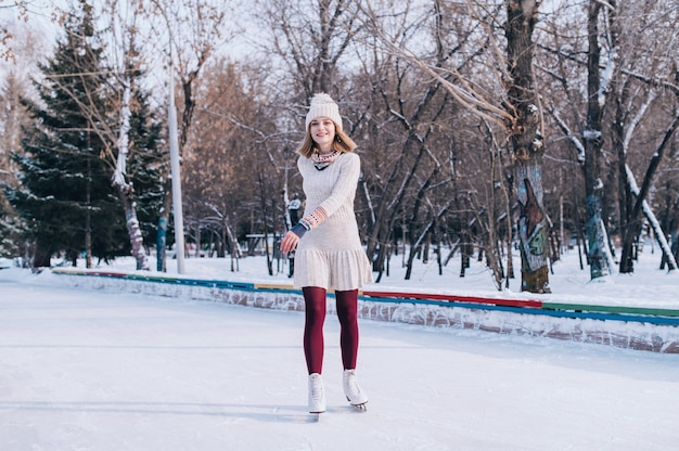 Young blonde caucasian girl in warm clothes skating on frozen lake in snowy winter park.