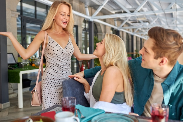 Young blonde caucasian woman in dress came to friends in cafe at birthday