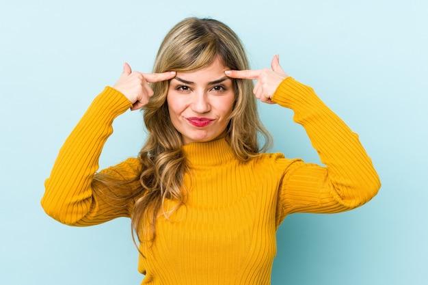 Молодая белокурая кавказская женщина сосредоточилась на задаче, держа указательные пальцы, указывая головой.