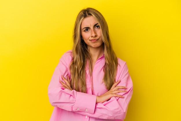 若い金髪の白人女性は不快に顔をしかめ、腕を組んでいます。