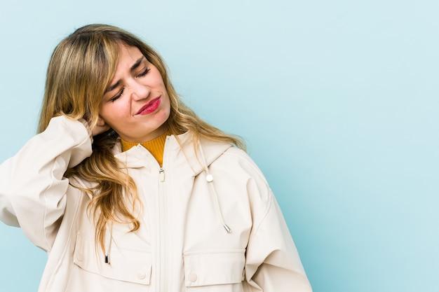 Молодая белокурая кавказская женщина испытывает боль в шее из-за стресса, массируя и касаясь ее рукой.