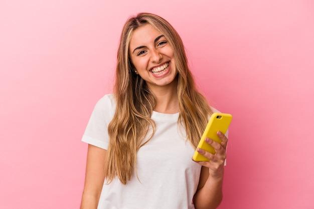 黄色の携帯電話を持っている若い金髪の白人女性は、幸せ、笑顔、陽気な孤立しました。