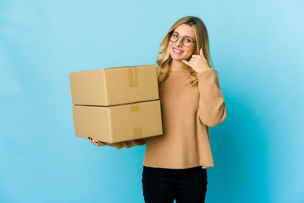 Young blonde caucasian woman holding boxes to move showing a mobile phone call gesture with fingers.