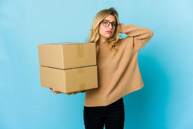 ショックを受けて動くために箱を持っている若いブロンドの白人女性、彼女は重要な会合を思い出しました。