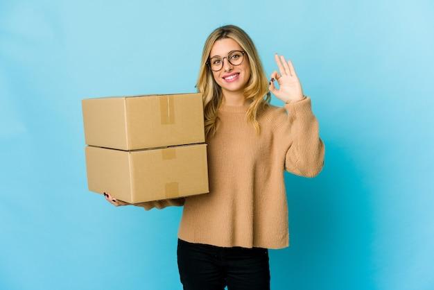 陽気で自信を持って移動するボックスを保持している若い金髪の白人女性は、okジェスチャーを示しています。