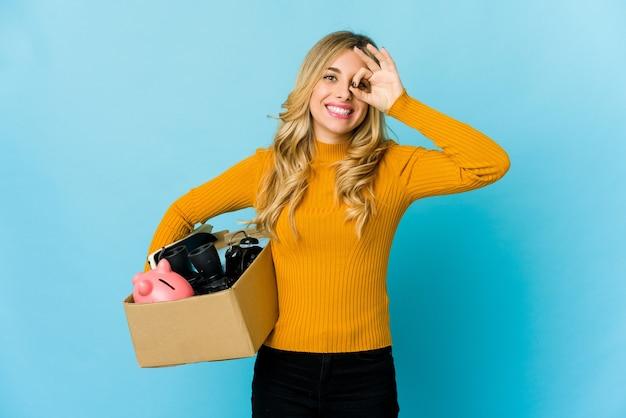目を動かし続けて興奮して動くために箱を持っている若いブロンドの白人女性。