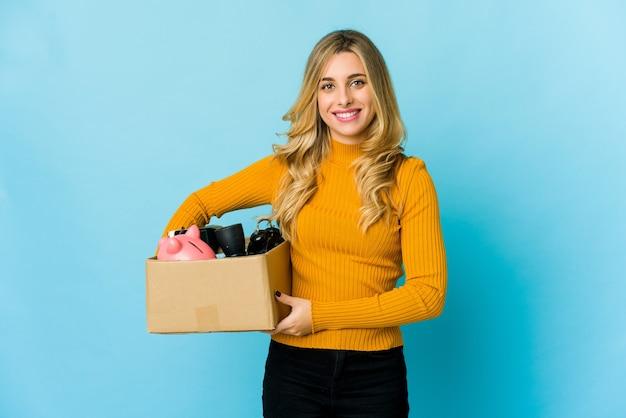 Молодая белокурая кавказская женщина, держащая коробки для перемещения, счастливая, улыбающаяся и веселая.