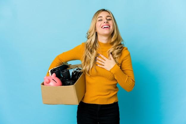 移動するために箱を持っている若い金髪の白人女性は、胸に手を置いて大声で笑います。