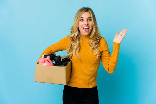 Молодая белокурая кавказская женщина, держащая коробки, чтобы переехать, получая приятный сюрприз, возбужденная и поднимающая руки.