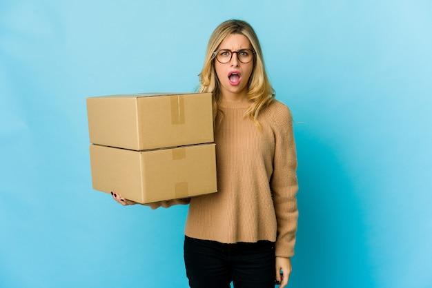 非常に怒って攻撃的な叫び声を移動するためにボックスを保持している若い金髪の白人女性。