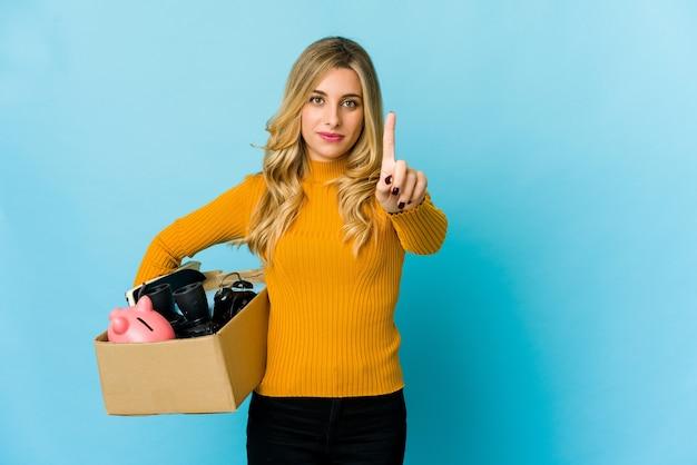 指でナンバーワンを示して移動するボックスを保持している若い金髪の白人女性。