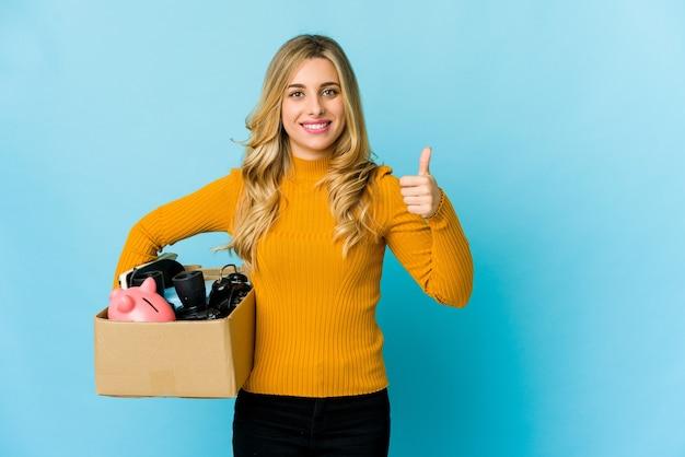 Молодая белокурая кавказская женщина, держащая коробки для перемещения, улыбается и поднимает палец вверх