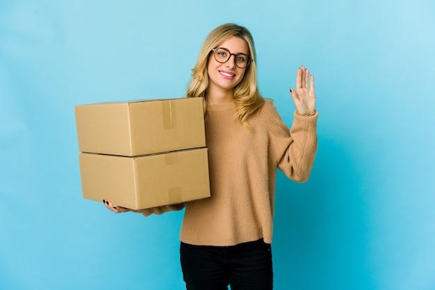 指で5番を示す陽気な笑顔を移動するためにボックスを保持している若い金髪の白人女性。
