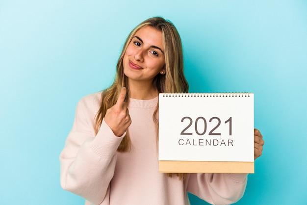 Молодая белокурая кавказская женщина продырявливает календарь, указывая пальцем на вас, как будто приглашая подойти ближе.