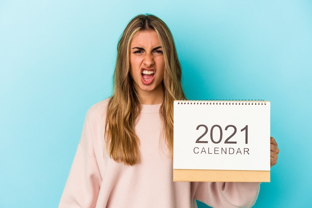 Young blonde caucasian woman holing a calendar isolated screaming very angry and aggressive.