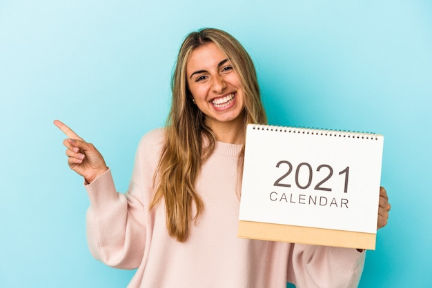 Young blonde caucasian woman holing a calendar isolated smiling and pointing aside, showing something at blank space.