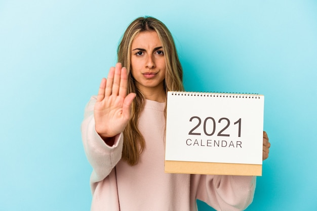 Young blonde caucasian woman holing a calendar isolated standing with outstretched hand showing stop sign, preventing you.