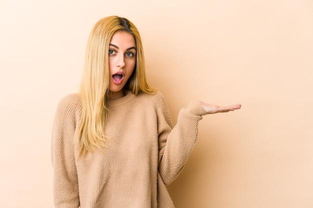 若い金髪の白人女性は、手のひらにコピースペースを持っていることに感銘を受けました。