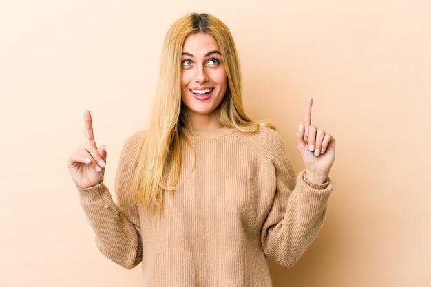 젊은 금발의 백인 여자는 빈 공간을 보여주는 두 앞 손가락으로 나타냅니다.