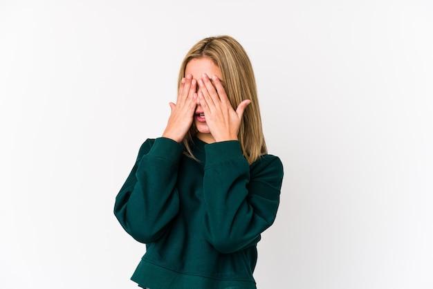 Молодая белокурая кавказская женщина изолировала испуганные глаза заволакивания руками.