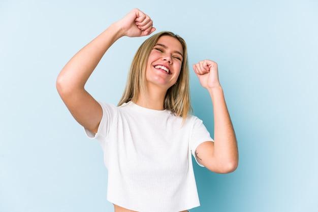 若い金髪白人女性は特別な日を祝って分離されたジャンプし、エネルギーで腕を上げる。