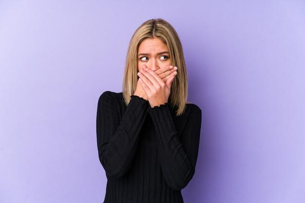 若い金髪白人女性は心配そうに見えて手で円錐形の口を分離しました。