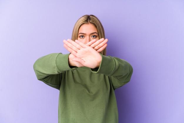 Молодая белокурая кавказская женщина изолирована, делая жест отрицания