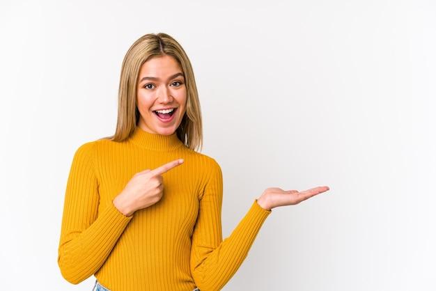 分離された若い金髪白人女性は手のひらにコピースペースを保持して興奮しています。