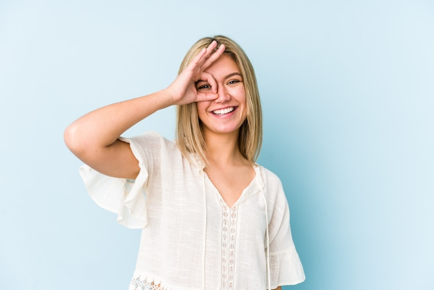Young blonde caucasian woman isolated excited keeping ok gesture on eye.