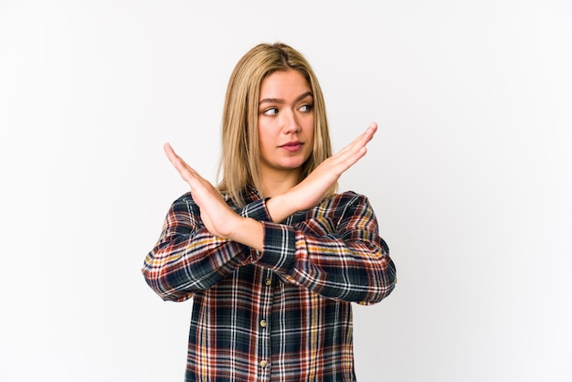 Young blonde caucasian woman isolated keeping two arms crossed, denial concept.