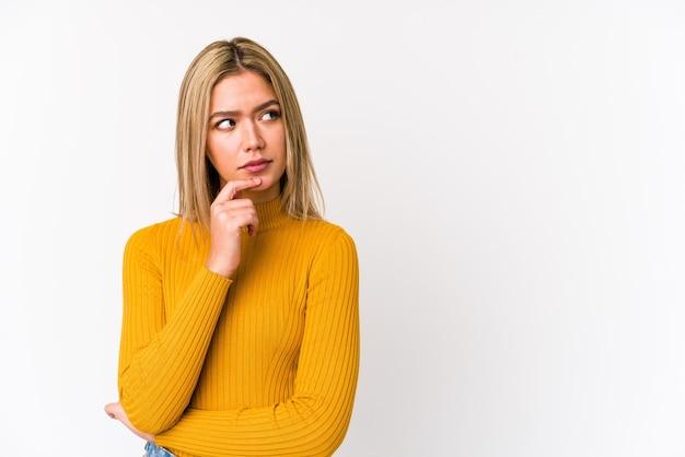 若い金髪白人女性は、疑わしく懐疑的な表現を横向きに探して分離しました。