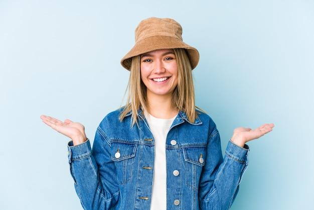 分離された若い金髪白人女性は腕でスケールを作る、幸せと自信を感じています。