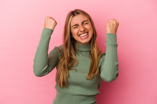 Молодая белокурая кавказская женщина, изолированная на розовом фоне, празднует победу, страсть и энтузиазм, счастливое выражение.