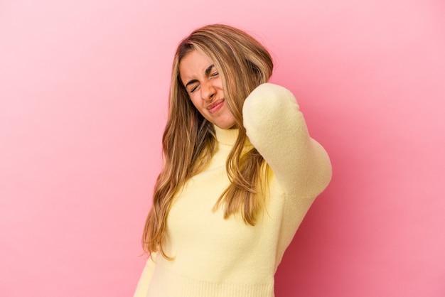 Молодая белокурая кавказская женщина изолирована на розовом фоне с болью в шее из-за стресса, массируя и касаясь ее рукой.