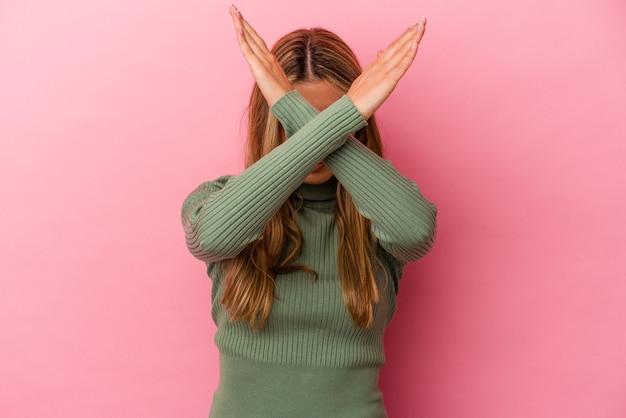 Молодая белокурая кавказская женщина изолирована на розовом фоне, держа скрещенными руками, концепцию отрицания.