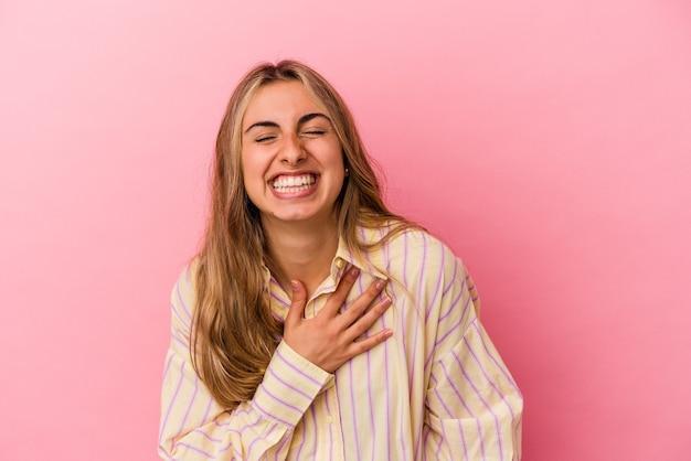 분홍색 배경에 고립 된 젊은 금발의 백인 여자 큰 소리로 가슴에 손을 유지 웃음.