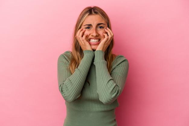 ピンクの壁に孤立した若い金髪の白人女性が泣いて、何かに不満、苦痛と混乱の概念。