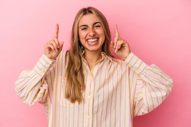 분홍색 벽에 고립 된 젊은 금발의 백인 여자는 빈 공간을 보여주는 두 앞 손가락으로 나타냅니다.