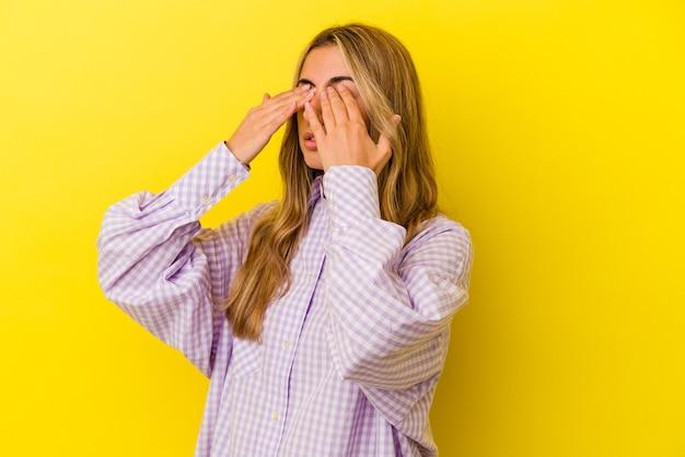 Молодая белокурая кавказская женщина, изолированная на желтом фоне, боится, закрывая глаза руками.