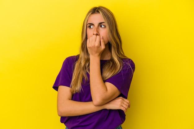 若い金髪の白人女性は、黄色の背景に爪を噛んで孤立し、神経質で非常に心配しています。