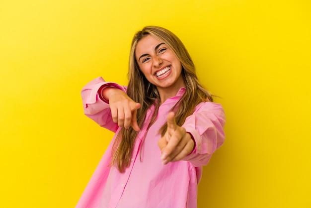노란색 배경 밝은 미소 앞을 가리키는에 고립 된 젊은 금발의 백인 여자.