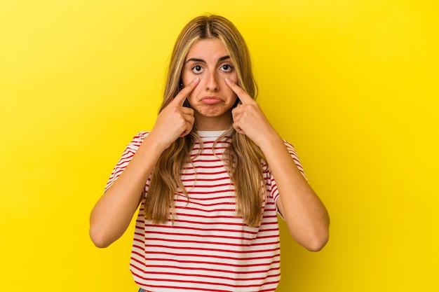 泣いて、何かに不満、苦痛と混乱の概念黄色の背景で隔離の若い金髪白人女性。