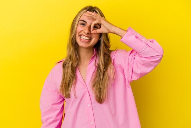 黄色の背景に分離された若い金髪の白人女性は、目に大丈夫なジェスチャーを維持して興奮しました。
