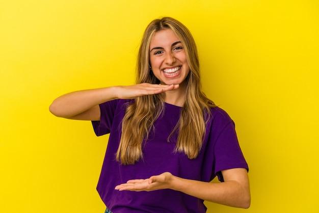 제품 프레 젠 테이 션 양손으로 뭔가 들고 노란색 배경에 고립 된 젊은 금발의 백인 여자.