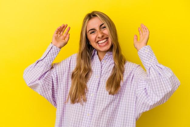 たくさん笑ってうれしそうな黄色の背景に分離された若い金髪白人女性。幸福の概念。