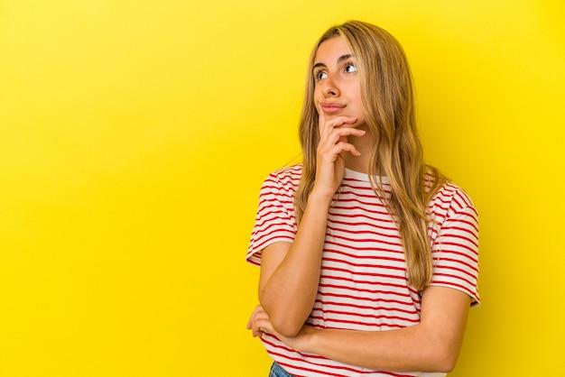 Молодая белокурая кавказская женщина изолирована на желтом фоне, глядя в сторону с сомнительным и скептическим выражением лица.