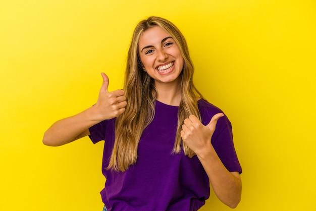 Молодая белокурая кавказская женщина изолирована на желтом фоне, поднимая пальцы вверх, улыбаясь и уверенно.