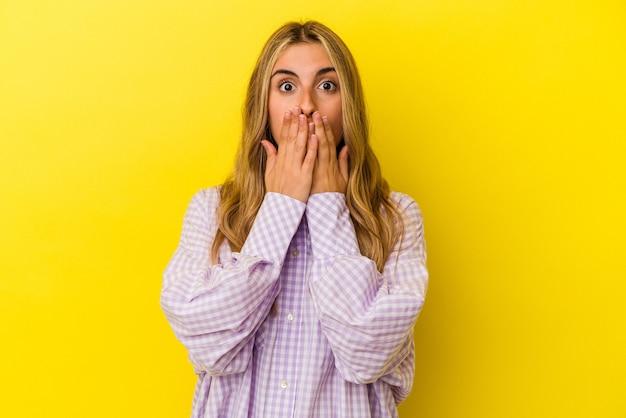 黄色の背景で隔離された若い金髪の白人女性はショックを受け、手で口を覆い、何か新しいものを発見することを切望しています。