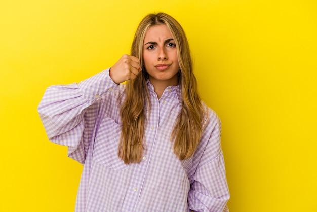 カメラに拳、攻撃的な表情を示す黄色の背景に分離された若い金髪白人女性。